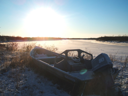Boat docked by frozen river